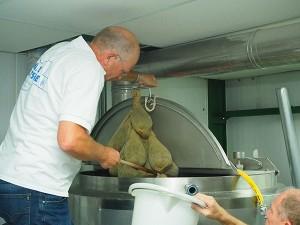 Sytze Hoogstins haalt de kruidenbuiltjes met gagel uit de kokend hete worttank. Loonbrouwer Gerrit Admiraal helpt hem daarbij, want de zakjess zijn na enkele minuten trekken loodzwaar geworden.