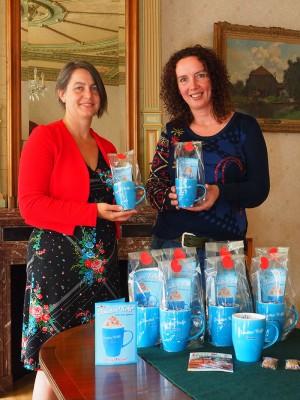 Directeur Iris Nutma van Museum Joure (links) en VVV-baas Petra van der Veen namen deze week de eerste Jouster Kofje mokken met recept, het boekje 'Proef Friesland' en dúmkes in ontvangst in de voormalige DE-directiekamer. De dames verkopen het exclusieve cadeautje in hun winkels aan de Midstraat voor €9,95.