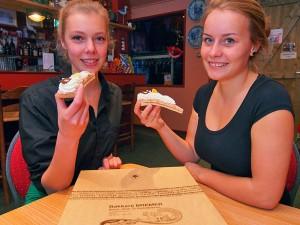 Sanne Ronner uit Ferwert (links, 18 jaar, studente design) en Marlies Douwes (17 jaar, HAVO 5-leerling uit Blija) weten het: de oranjekoek van bakker Bremer is altijd goed voor complimenten. De dames hebben een bijbaantje in het restaurant van Seedykstertoer in Marrum.